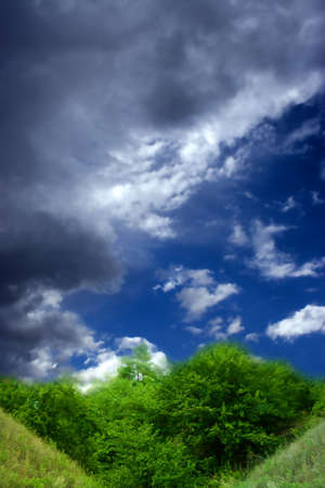 colorful cloudscape: beautiful clean bright sky on green hill and herb Stock Photo