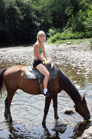 beautiful making look younger girl sits in saddle on horse photo