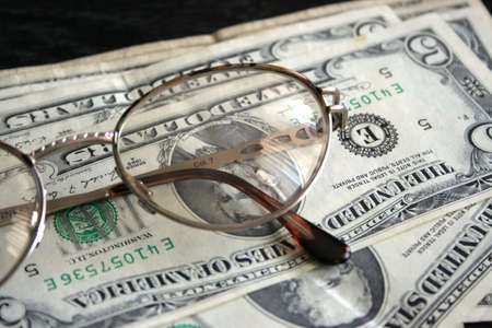 gentile: paper dollar bills and spectacles for correcting the vision Stock Photo