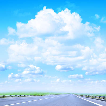 sectoring: road and grassy year landscape on background brightly blue sky Stock Photo