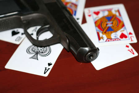 gun and playing cards on table in casino