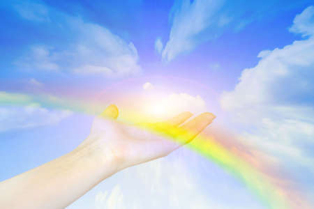 offering: rainbow on hand of the person on background shining sky  Stock Photo