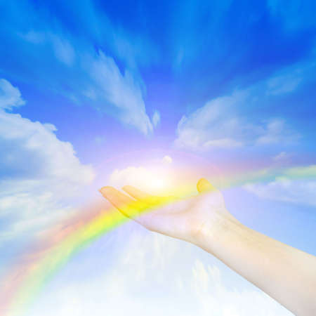 inviting: rainbow on hand of the person on background shining sky  Stock Photo