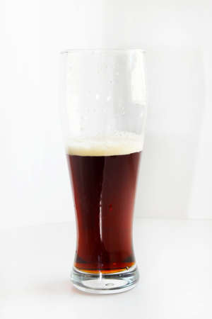 scene spume on surface dark beer in glass photo