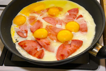 preparation fried eggs with bacon as matutinal feeding photo