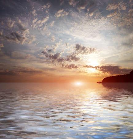 太陽の暗い空の下でのシーンの海の表面 写真素材