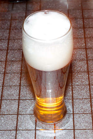 abstract high glass with light beer stands on the table photo