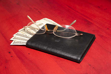 path to wealth: leather purse, old glasses and paper dollars