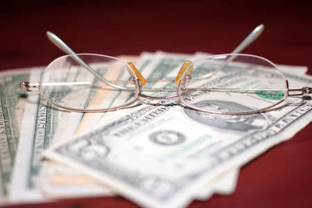 glasses for vision correction and a small pile of dollars photo