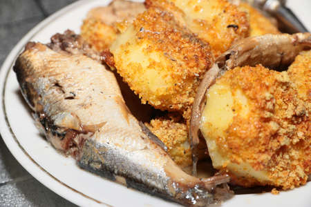 slices of smoked sprats canning and roasted potatoes photo