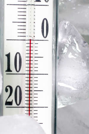glass thermometer for measuring of temperature and ice photo