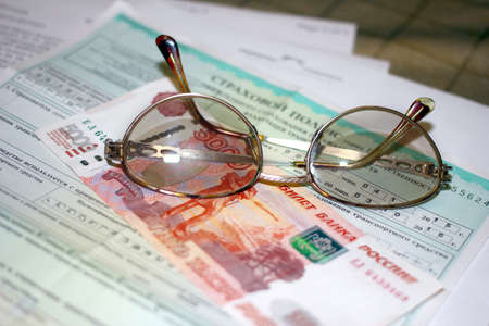 insurance themes: Russian money, glasses and papers for auto insurance Stock Photo