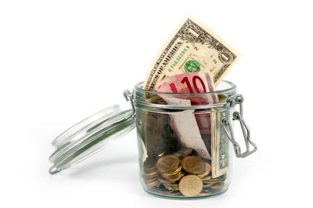 stack of dollar bill: small coins and paper notes in a glass jar