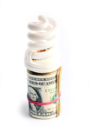 twisted bundle of dollars and a lamp for lighting Stock Photo