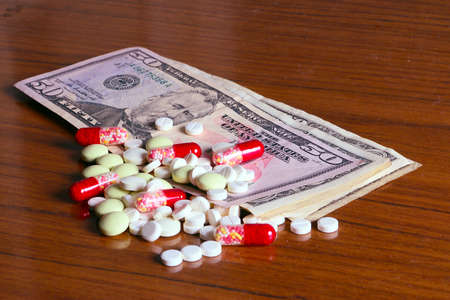 paid medicine: Dollar paper banknotes and medicine drugs and tablets as part of paid health care and treatment