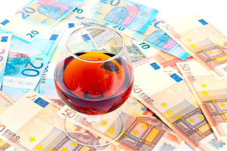 a small pile of paper euro banknotes and a glass of strong alcoholic drink