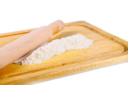 una pequeña cantidad de harina en una tabla de cortar de madera y rodillo