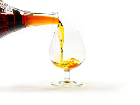 poured: strong alcohol drink is poured from a bottle into a glass as a preparation for the holiday
