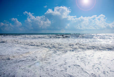 high waves and strong sea tide during a storm under sunny skies