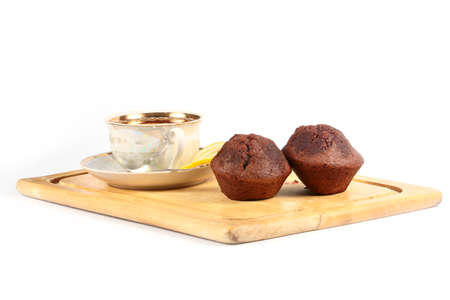 morning freshly baked chocolate cupcakes and porcelain cup of hot tea with a slice of lemon on a wooden tray