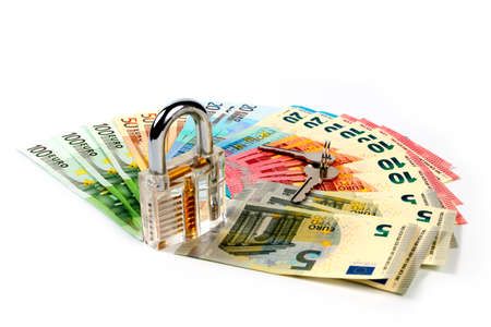 A small pile of euro banknotes and a padlock with keys as an element of the protection of the commercial economic system Stock Photo