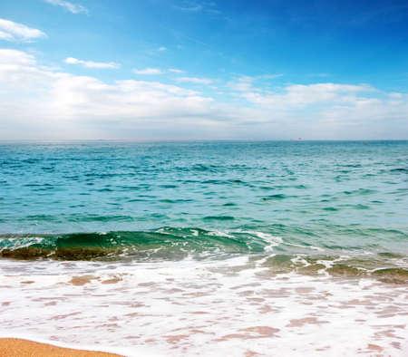 A beautiful ocean surface under a sunny skyline with a sandy beach