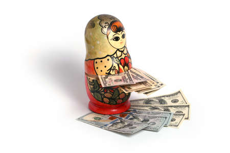 muñecas rusas: Russian national wooden toy stands on a pile of American dollars Foto de archivo