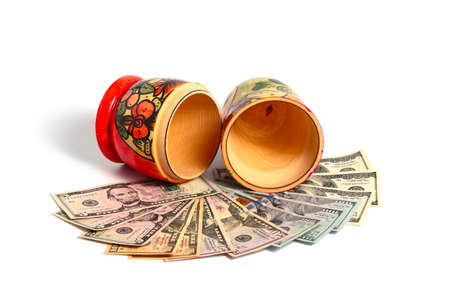Russian national wooden toy stands on a pile of American dollars Stock Photo