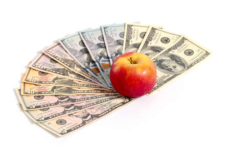 A ripe fresh red apple lies on a pile of American dollars