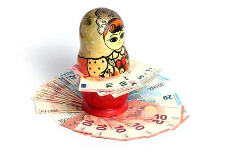 muñecas rusas: Russian national wooden toy stands on a pile of European paper bills euro Foto de archivo