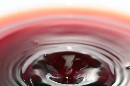 Ripples on the surface of a dark red liquid in a container after its pouring Stock Photo