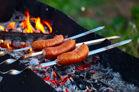 Cooking fatty meat sausages on an open fire in the brazier grill