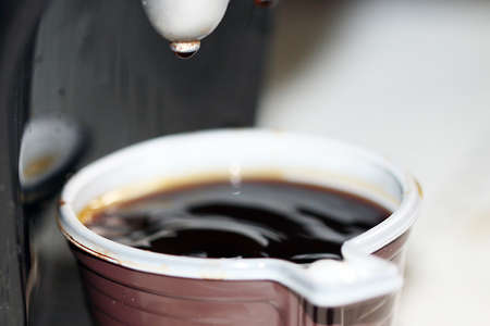 Drops and a jet of hot coffee in a cup of coffee