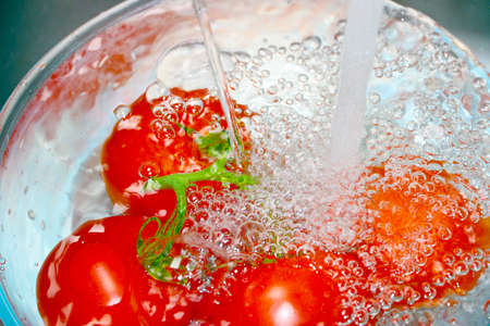 Beautiful ripe fresh red tomatoes under a stream of water in a glass bowl