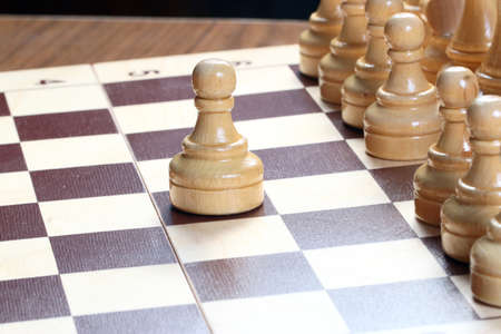 rival: Light and dark wooden lacquered figures and a chess board