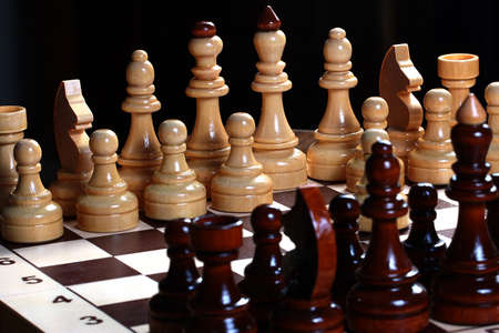 rival: Dark and light wooden chess pieces stand on a blackboard