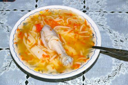 Gekookte heup van een vogel en pasta in een bord met kippensoep Stockfoto