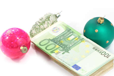 glass Christmas toys and a bundle of paper euro bills Stock Photo