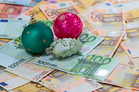 glass Christmas toys on paper euro banknotes