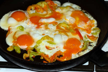 cooking fried peppers in fried eggs for breakfast 写真素材