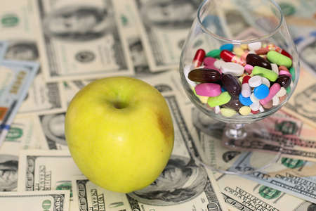 fresh apple and medicine on paper denominations dollars