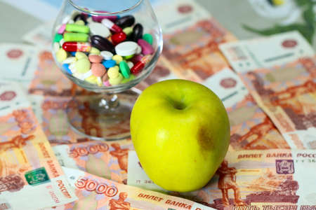 pills medication in a glass and apple on Russian paper banknotes ruble