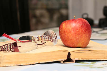 lovely ripe delicious apple and pages of an old book Stock Photo