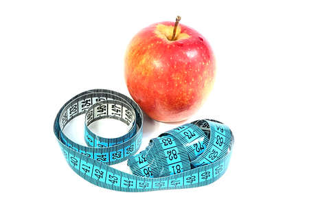 a beautiful ripe fresh apple and a measuring tape as part of fitness