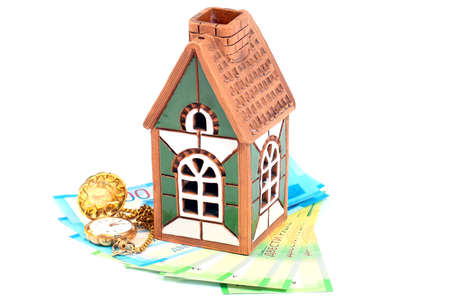 old pocket watches, Russian paper bills and a souvenir house as an illustration of a mortgage