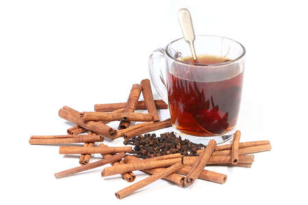 dried spices seasoning cloves and cinnamon next to a cup of hot black tea