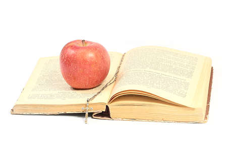 a ripe red apple on the pages of an old book and a gold cross on a chain
