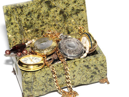 antique pocket watch and a pile of precious items in a stone casket