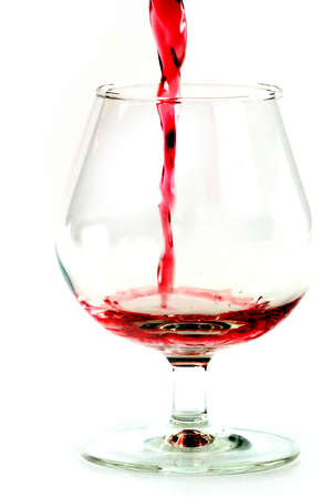 bright red wine is poured into a glass for drinking