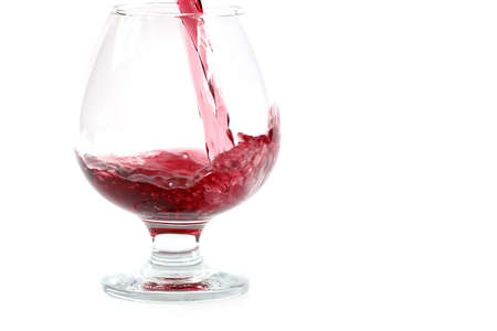 A fine red wine is poured into a transparent glass